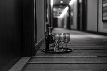 grayscale image of a hotel hallway and a tray of champagne with glasses