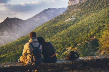 couple sitting while facing the mountain